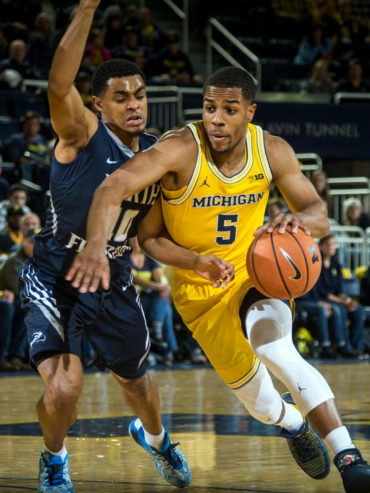 North Florida guard Osborn Blount, left, defends Michigan guard Jaaron Simmons (5) in the first half of an NCAA college basketball game at Crisler Center in Ann Arbor, Mich., Saturday, Nov. 11, 2017. (AP Photo/Tony Ding)
