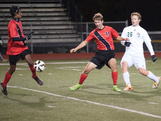 Samuel Paul tries to pass the ball to his teammate Bailey Craner for Mansfield Christian during their regional semi-final game against Elyria Catholic Wednesday evening at the Ashland Community Stadium. Mansfield was winning 1-0 at the half.