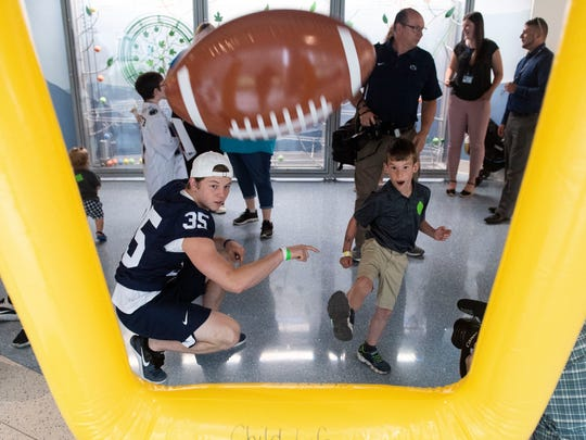 Owen Zeager, 7, kicks an inflatable ball through goalposts with help from Penn State's Justin Neff during the players' visit to the children's hospital.
