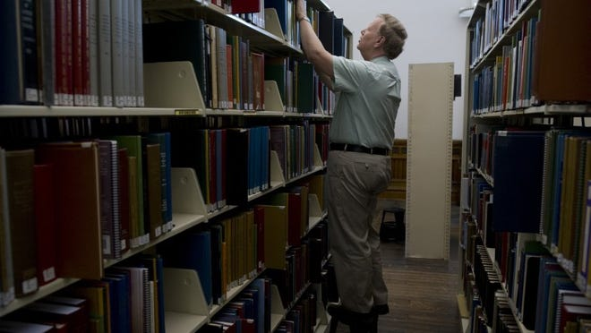 DENNY SIMMONS / COURIER & PRESS Stan Schmitt reshelves a reference book at Willard Library Thursday afternoon. Since reference books can't be 'checked-out,' the library asks visitors to not reshelve the books on their own so the staff can manually scan them before placing them where they belong. This allows the library to know which and how many of the books are being used by the public.