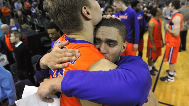 JASON CLARK / COURIER & PRESS   A tear rolls from the eye of D.J. Balentine after he became emotional while speaking to the fans as he shares a hug with fellow University of Evansville senior Egidijus Mockevicius on senior night after the game at the Ford Center in Evansville Saturday.  Northern Iowa won the final game of the regular season 54-52.