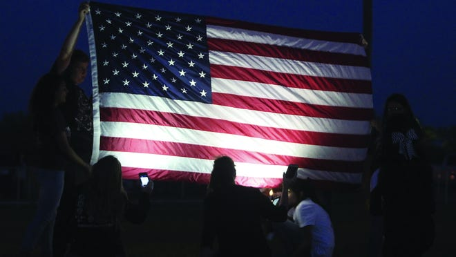 Students from Paint Rock and Loraine high school hold up the American flag during a short ceremony marking the 15th anniversary of Sept. 11, 2001 at Friday night's game in Paint Rock. Michelle Gaitan/Standard-Times