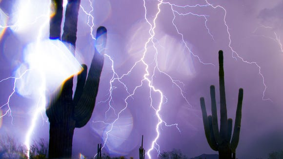 Rain drops cover the camera lens while lightning strikes over saguaros during a monsoon storm in east Mesa July 26, 2014.