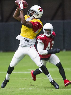 John Brown pulls in a pass as cornerback Mike Jenkins, 43, defends at a recent Cardinals practice.