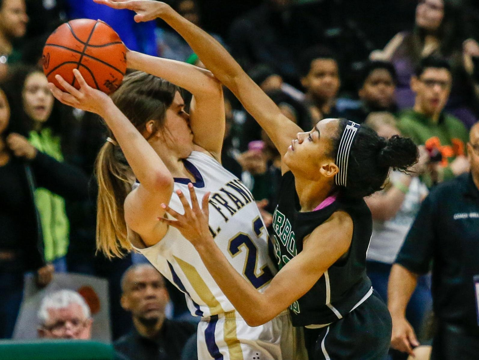 Traverse City St. Francis' Annie Lyman tries to pass the basketball while being guarded by Ypsilanti Arbor Prep's Adrienne Anderson.
