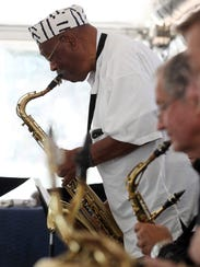 Roger Hogan stands up to play a saxophone solo Saturday,