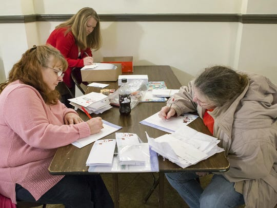 Jaycees letter elves write notes from Santa to a local child at the Jaycee's clubhouse in Wilmington on Monday night.
