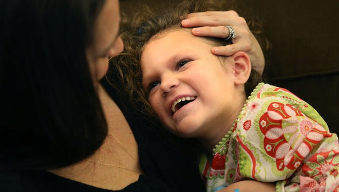 Dana Gieselmann evokes a smile as she tickles her daughter Milla, 6, who was diagnosed with Batten disease at 4 1/2 years old.