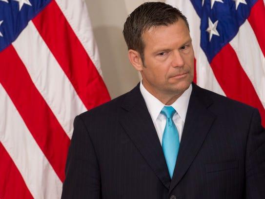 Kansas Secretary of State Kris Kobach listens as President