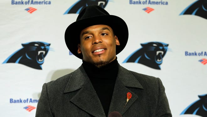 Carolina Panthers quarterback Cam Newton wears a black coat and hat as he talks with reporters during a post-game news conference after an NFL football game against the Seattle Seahawks, Sunday, Dec. 4, 2016, in Seattle.
