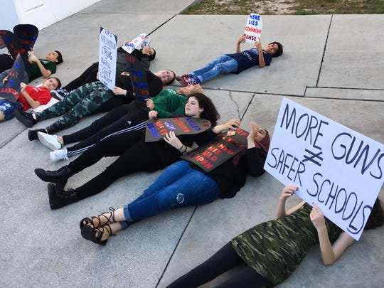 "In an April 2018 photo, a group of students and some teachers and parents staged a small ""die-in"" protest before a town hall at Palm Bay High School auditorium. It was the first of three such meetings to get public input on a proposed marshal program to arm school staff."