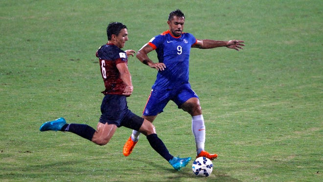 India's Robin Singh, right, and Guam's Mason Douglas in action as it rains during their 2018 FIFA World Cup qualifying soccer match in Bangalore, India, Thursday, Nov. 12, 2015. India won the match 1-0.