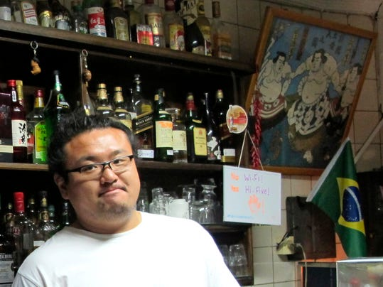 """In this June 10, 2014 photo, Wagner Yoshihiro Higuchi tends the Bar Kintaro, with a woodblock print of Japan's quintessential sumo sport and a Brazilian flags hanging on the wall, in Asian-flavored Libertade district of Sao Paulo, Brazil. Brazil hosts the world's largest ethnic Japanese population outside Japan -1.5 million, or half of the roughly 3 million scattered around the globe.  Many """"Nikkei"""" like the Higuchi brothers have forged vibrant hybrid identities where sumo meets samba.  (AP Photo/Joji Sakurai)"""