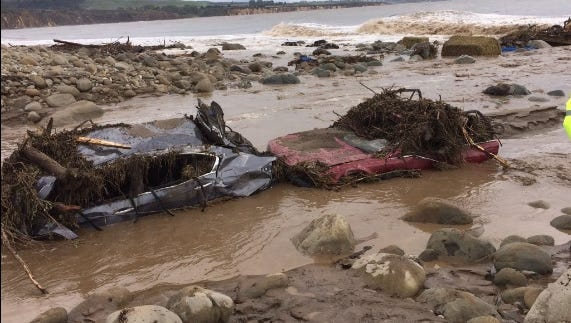 Destroyed vehicles sit caked in mud at the river mouth on El Capitan Beach in Santa Barbara, Calif., on Jan. 20, 2017.
