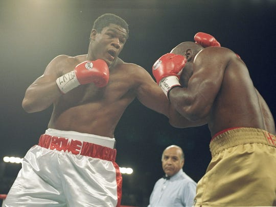 Riddick Bowe (left) lands a left blow on Evander Holyfield