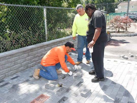 Virginia Norfleet, right, directs a mason as he installs