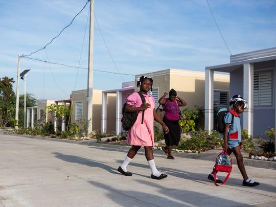 Children living in Haut Damier village, built by USAID, walk to school on Dec. 11, 2014.