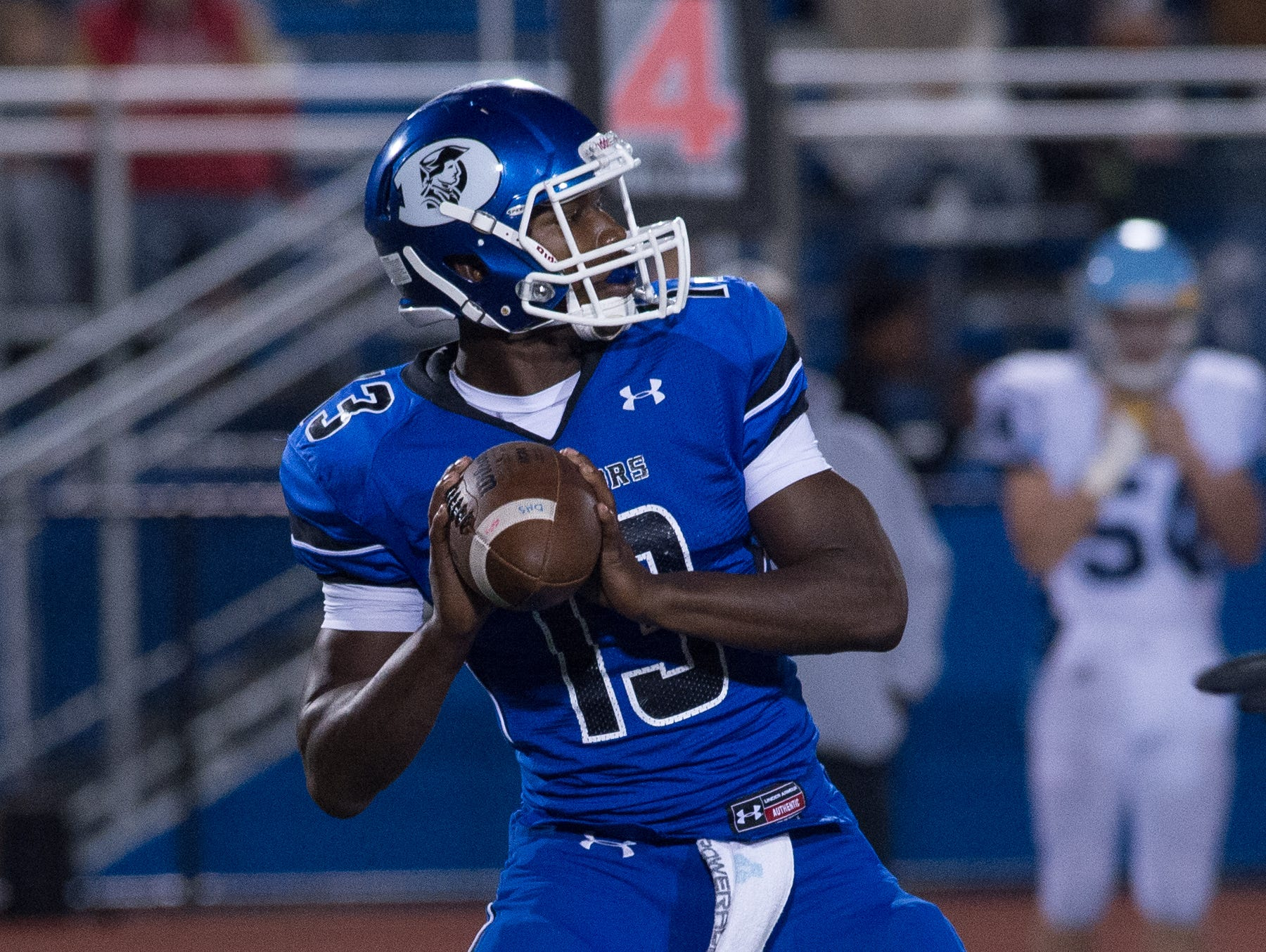 Dover's quarterback Jordan Magee (13) looks for a receiver in their home game against Cape Henlopen.