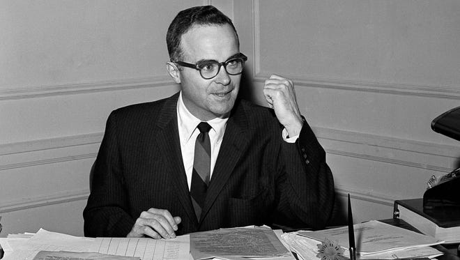 In this March 22, 1961, file photo, Walter Byers, executive director of the NCAA, sits at his desk in Kansas City, Mo.