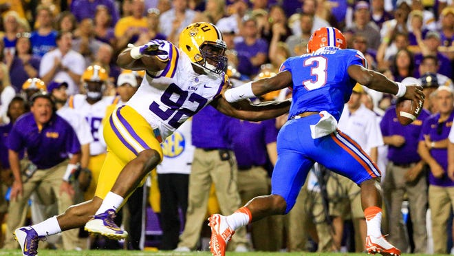 LSU Tigers defensive end Lewis Neal (92) pressures Florida Gators quarterback Treon Harris (3) during the second quarter of a game at Tiger Stadium.