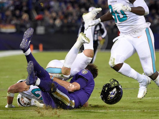 This Oct. 26, 2017 photo shows Miami Dolphins middle linebacker Kiko Alonso, top left, colliding with Baltimore Ravens quarterback Joe Flacco in the first half of an NFL football game in Baltimore. In their return from a three-day break, the Ravens provide an eagerly anticipated update on Flacco, who sustained a concussion in a 40-0 win over Miami and hopes to be ready for Sunday's game at Tennessee. (AP Photo/Nick Wass)