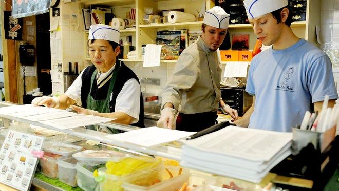 File photo - Noble Fish Sushi Chefs Kazu Tomobe, left, Chris Kwasny and Marc Dobaczewski prepare customers orders.