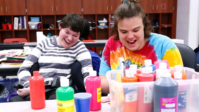 Heidi Cassidy, 19 and Paige Monastere, 18, work on a Mother's Day craft project at Shelby High School on Thursday. The two are students with disabilities who will be attending their school's prom for the first time this Saturday.