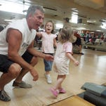 David Jorns of Hattiesburg, his daughter, Alyiah, 28 months, and her friend Meghean McCardle, 4, enjoy a night out bowling at Hub Lanes in Hattiesburg on Friday, Sept. 9, 2005. The family was at a birthday party on their first night out since curfew broke.