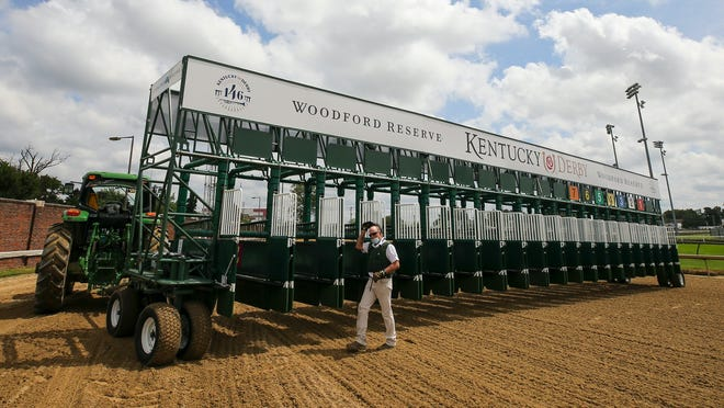 Crews ready a new starting gate at Churchill Downs on Tuesday, Sept. 1, 2020, in Louisville, Ky. The starter and assistant starters were giving the new gate a test run for the mile-and-a-quarter race. The new starting gate will allow 20 horses to be loaded for the Kentucky Derby. The track has previously used two gates to accommodate the large field for the event. The gate will be used only for the Kentucky Derby.