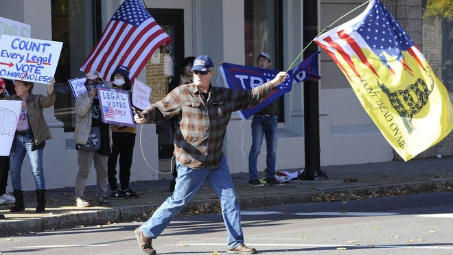 A supporter of President Donald Trump records himself while crossing an intersection during a rally protesting the counting of mail-in ballots in Wilkes-Barre, Pa., Friday.
