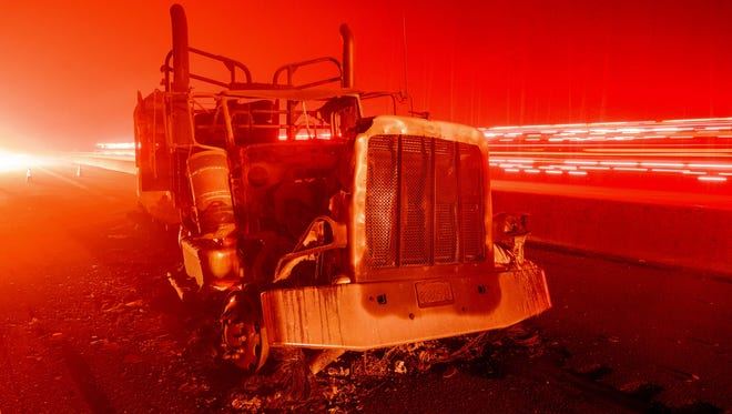 A fire vehicle passes by an abandoned burned out truck along Interstate 5 after the Delta Fire tore through the region and jumped the road in Delta, Calif. on Sept. 5, 2018.