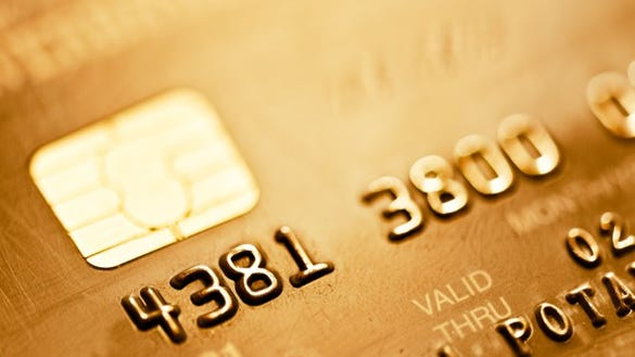 Close-up of credit card EMV chip and partial number on front of card.