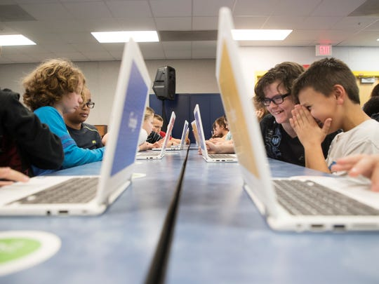 Gulf Coast Elementary School students, Ryan Blexrud, right, and Landon McCarthy take part in Google's CS First Roadshow teaches kids about the importance of STEM education through an interactive coding presentation.