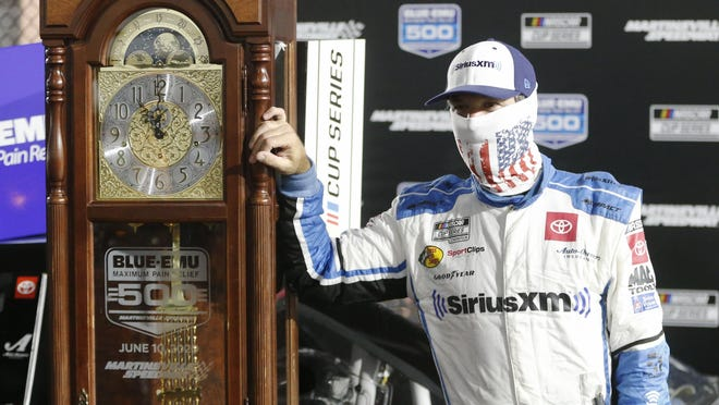 Martin Truex Jr. poses with his grandfather clock trophy after winning a NASCAR race Wednesday in Martinsville, Va.