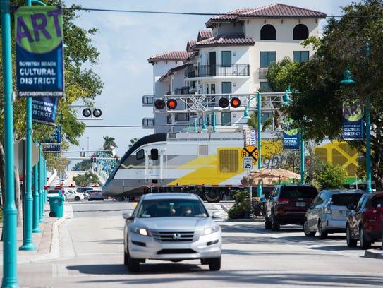 A Brightline train traveling north crosses East Ocean Avenue and Northeast 4th Street in Boynton Beach.