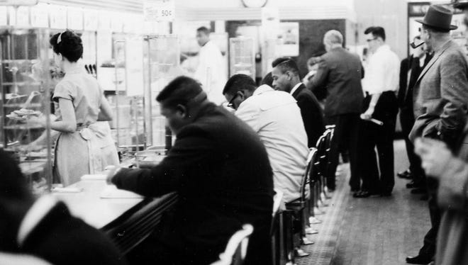 """In this February 1960 file photo, people take part in a civil rights """"sit-in"""" protest at the lunch counter in McCrory's in Rock Hill, S.C. A judge has tossed out the convictions of nine on Wednesday."""