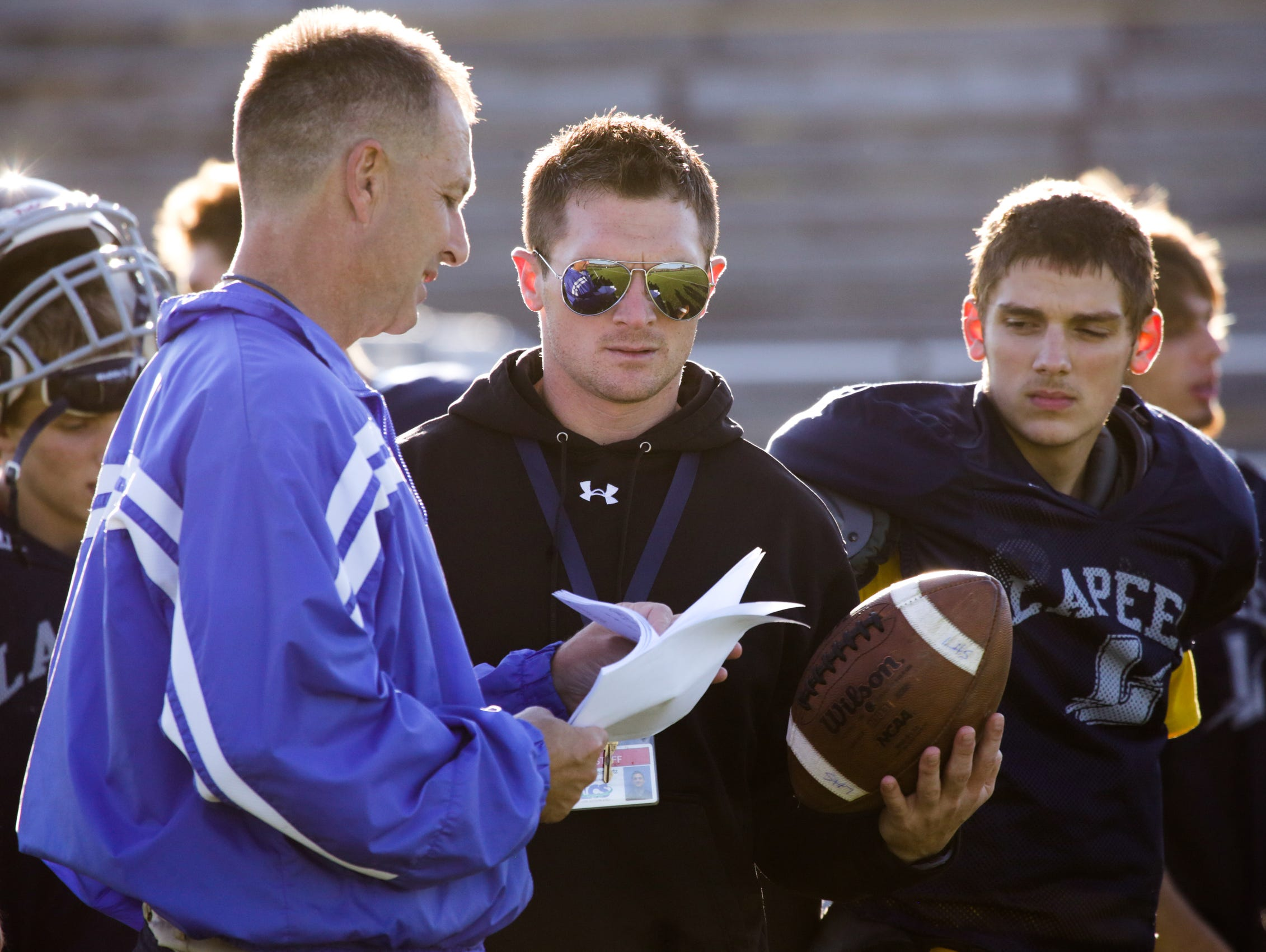 Lapeer High School head football coach Mike Smith (left) and offensive coordinator Jake Weingartz (center) discuss plays on Monday September 22, 2014 during varsity football practice at Lapeer High School in Lapeer, MI . This is the first year for Lapeer High School after Lapeer West and East merged. The blended team is off to a 3-0 start. Mike Smith, who was West's coach, is the coach and Jake Weingartz, who was East's coach, is the offensive coordinator. Ryan Garza / Detroit Free Press