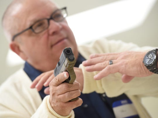 Paul Murray Jr. is trained in the proper technique of racking the slide of a handgun during a training course offered by Gary Smith, owner of Point Blank Defense at the York Township park building on Saturday, Oct. 15, 2016.