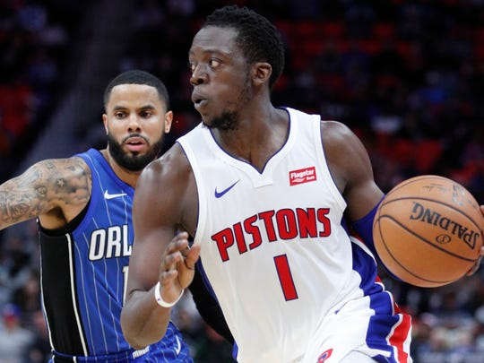 Pistons guard Reggie Jackson (1) dribbles by Magic guard D.J. Augustin (14) during the fourth quarter of the Pistons' 114-110 win on Sunday, Dec. 17, 2017, at Little Caesars Arena.