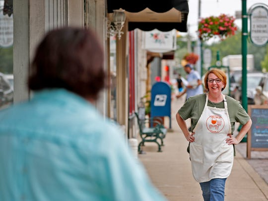 Peggy Kumler, left, walks up to greet her business neighbor, Robbin Wilson, from All Local, outside Kumler's Corner Cottage, on the downtown Noblesville Square, Friday, July 20, 2018.