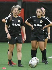 Dani Evans (left) and Madison Schupbach wait during