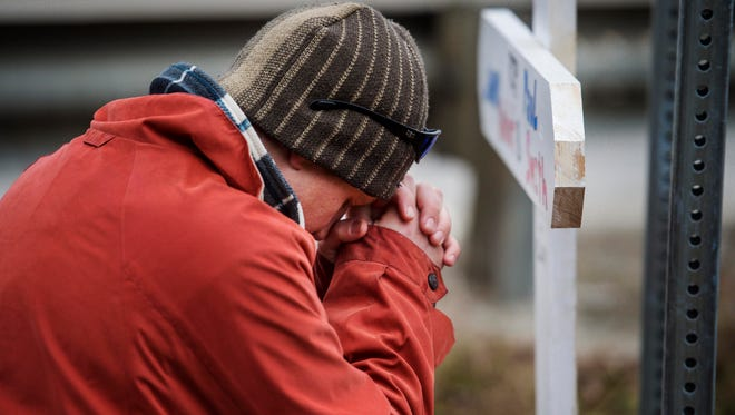 Chris Koonz of Wolcott offers a brief prayer on Monday, November 28, 2016, on Route 15A in Morrisville near where Lenny Audet and Paul Smith died Saturday when their car plunged into the Lamoille River .