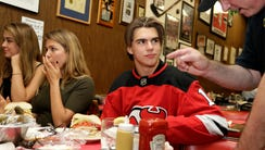New Jersey Devils' Nico Hischier talks with an owner