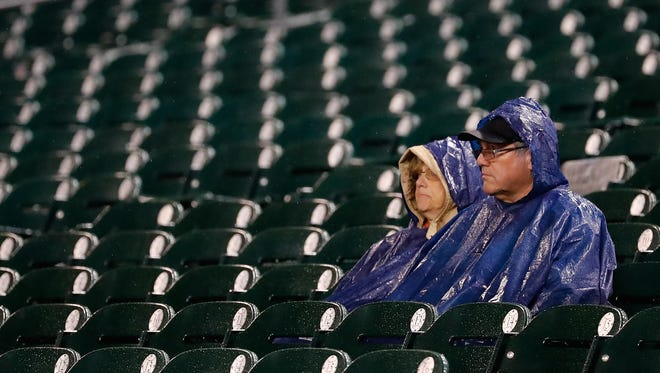Baseball fans wait for the rain to stop during a game between the Cleveland Indians and the Detroit Tigers on Sept. 28, 2016, at Comerica Park in Detroit.