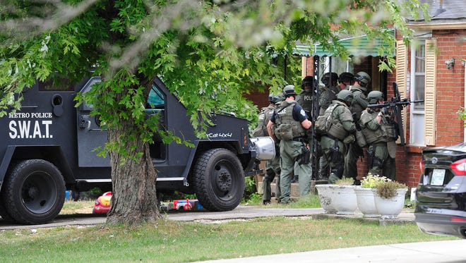 The SWAT team goes in and secures the house where three suspects were taken into custody earlier from an overnight crimes spree comes to end on Hinkle Drive in north Nashville, Tenn. September 25, 2015.