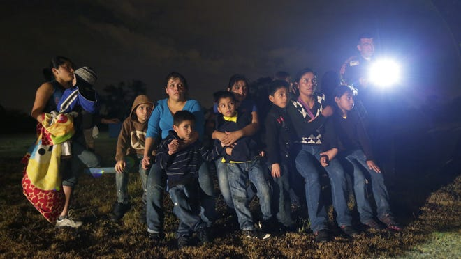 A group of immigrants from Honduras and El Salvador who crossed the U.S.-Mexico border illegally as they are stopped in Granjeno, Texas.