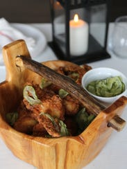 Honey-battered fried chicken and house-made pickles are served in a wooden basket at Chef Max Hardy's restaurant, River Bistro, in northwest Detroit.