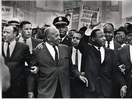 The Rev. Martin Luther King Jr. waves as he leads the