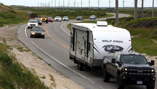 Vacationers head north on NC 12 on Hatteras Island, N.C., on  July 28, 2017.  An estimated 10,000 tourists face a noon deadline Friday for evacuating the island on North Carolina's Outer Banks after a construction company caused a power outage, leaving people searching for a place to eat, stay cool or to resume interrupted vacations.