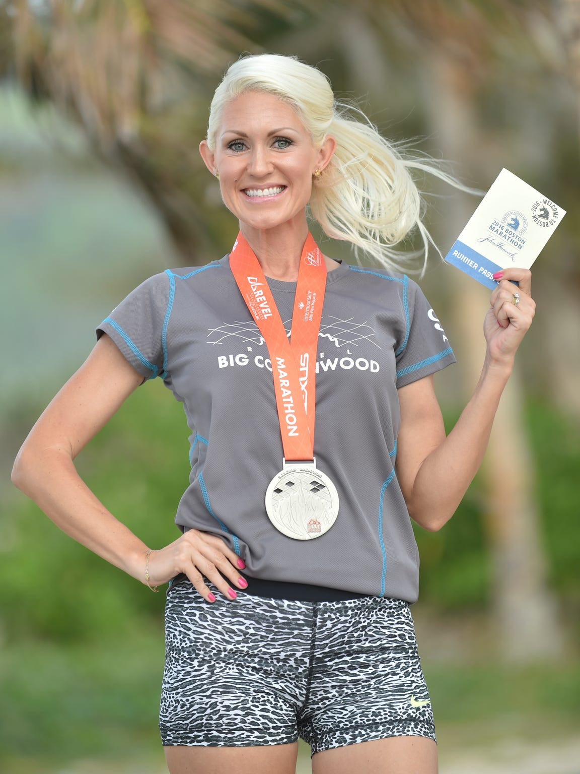 Stephanie Clark proudly displays her Runner's Passport to the upcoming Boston Marathon at Asan Beach Park on April 7.